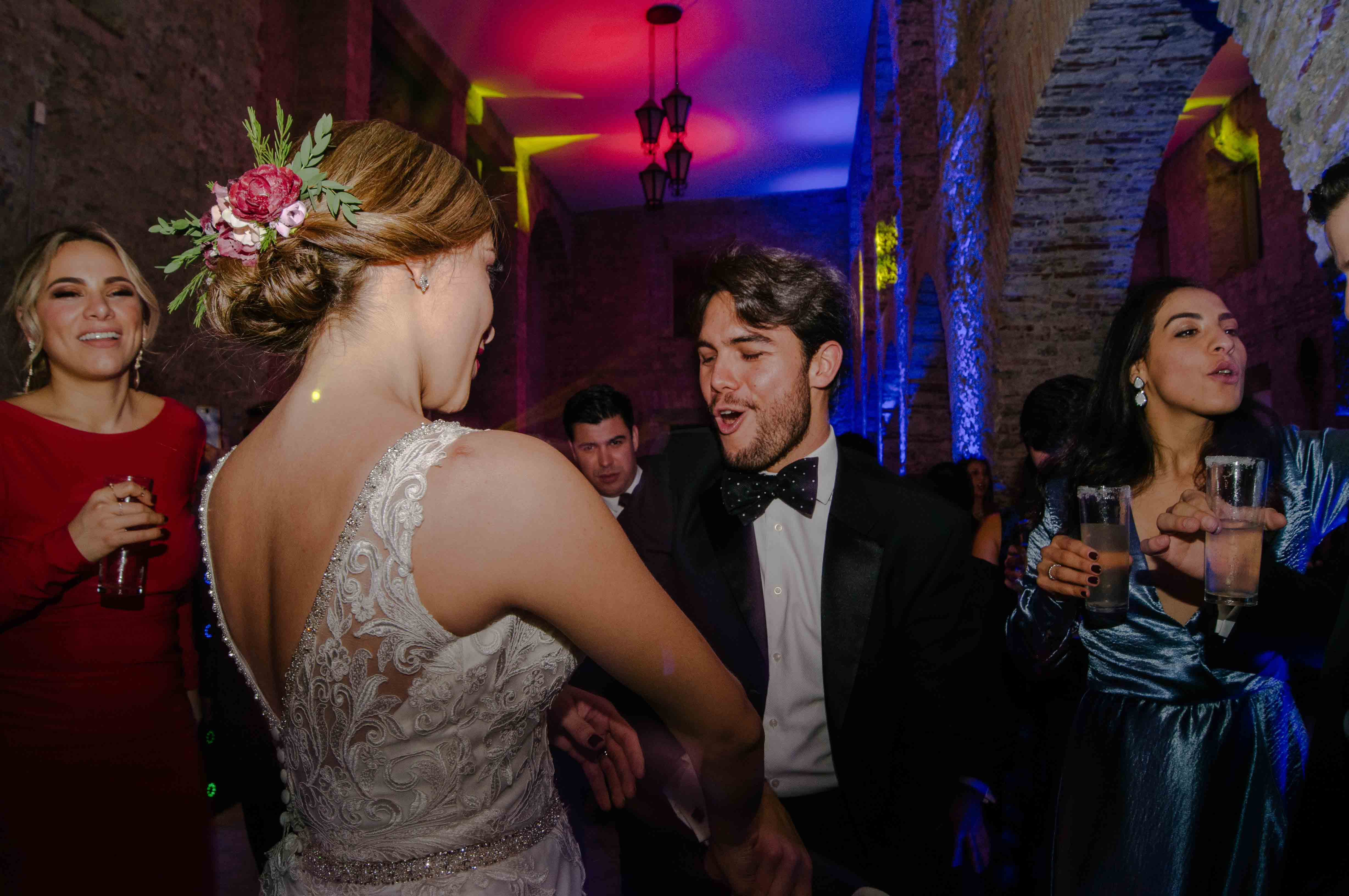 Man with tuxedo dancing with bride in nocturnal ambiance