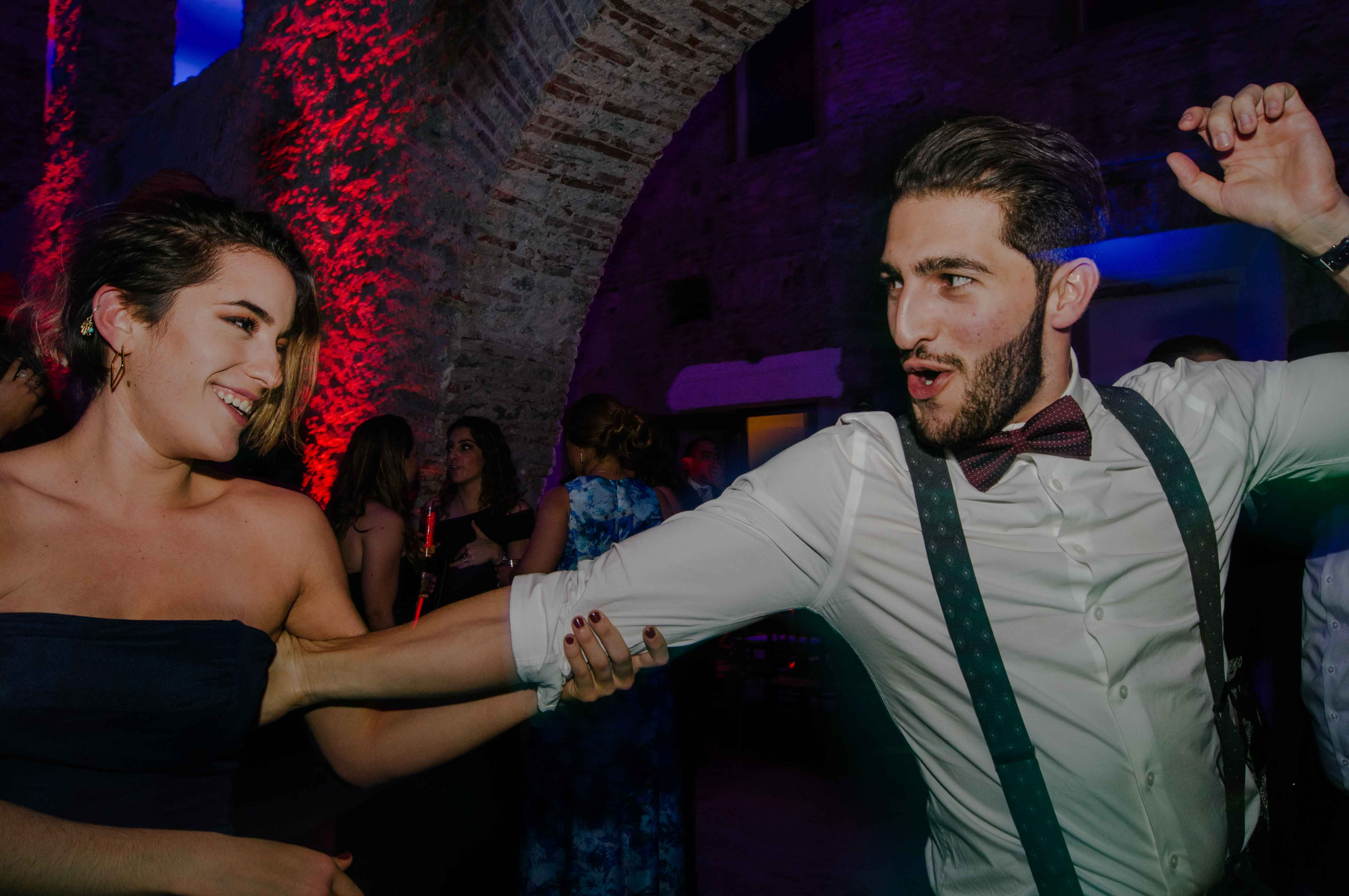 Man with suspenders and bowtie dancing with lady in nocturnal ambiance