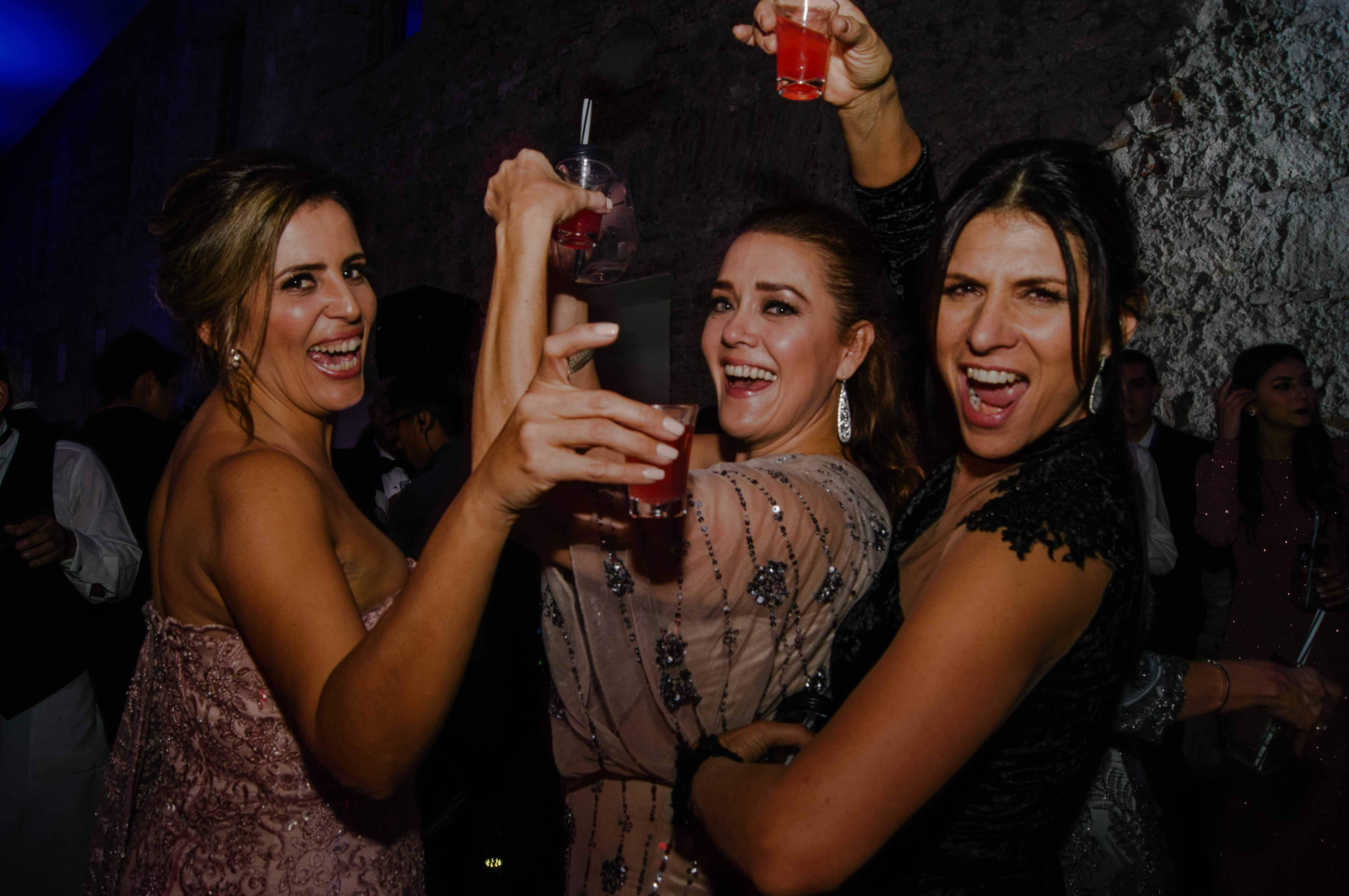 Three women holding red shots while dance in wedding