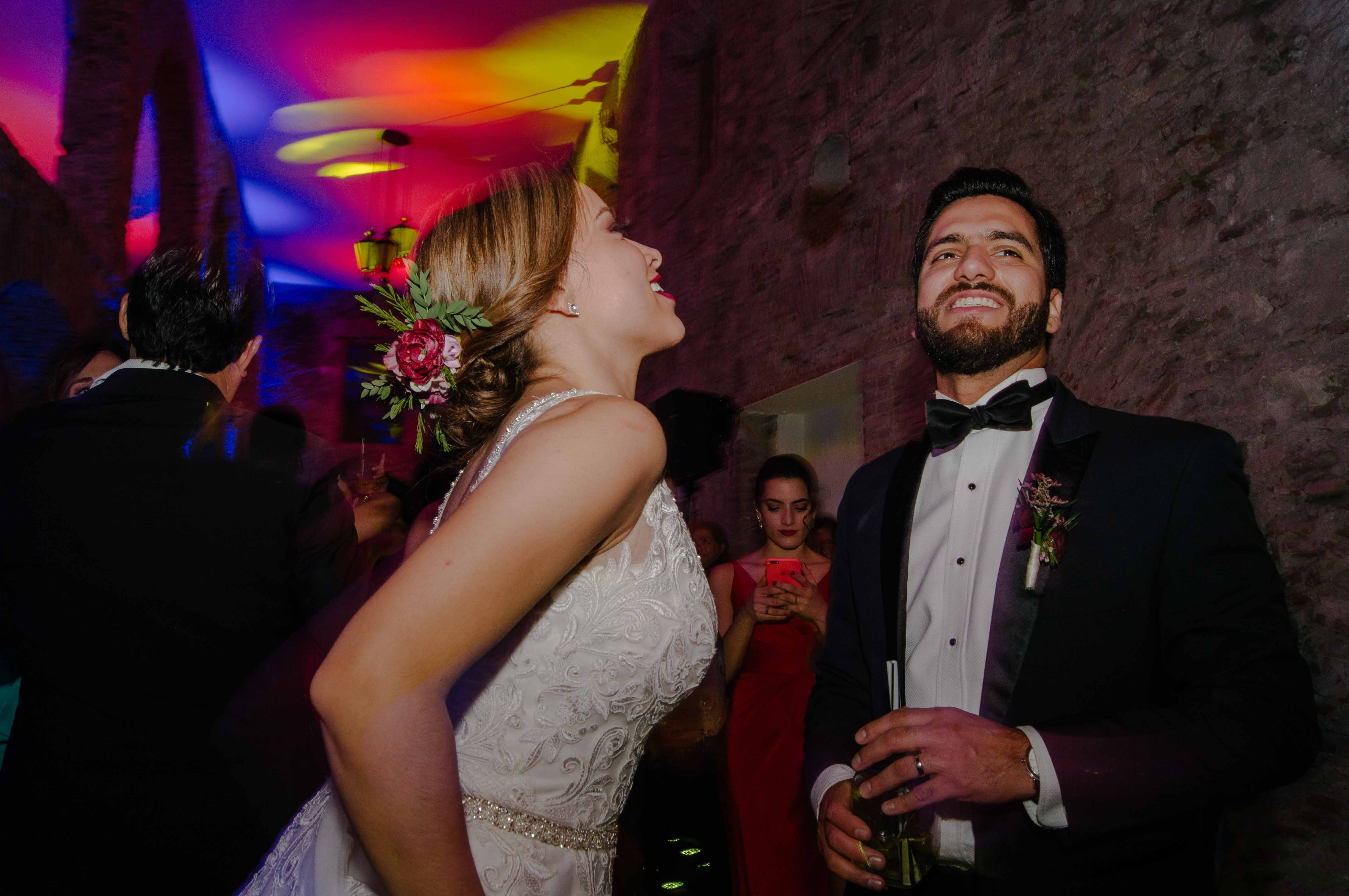 Bride and groom dancing with glasses in wedding party